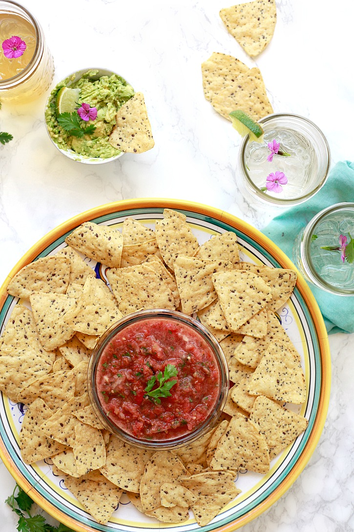 Beautiful platter of fresh tomato salsa, multigrain chips, and guacamole served with cold drinks.