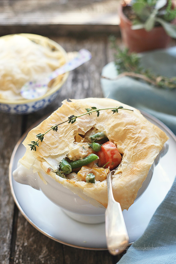 A small pot pie filled with green beans, carrots, peas, and squash covered with phyllo dough.