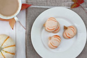 Pumpkin French Macarons on a plate with leaves.