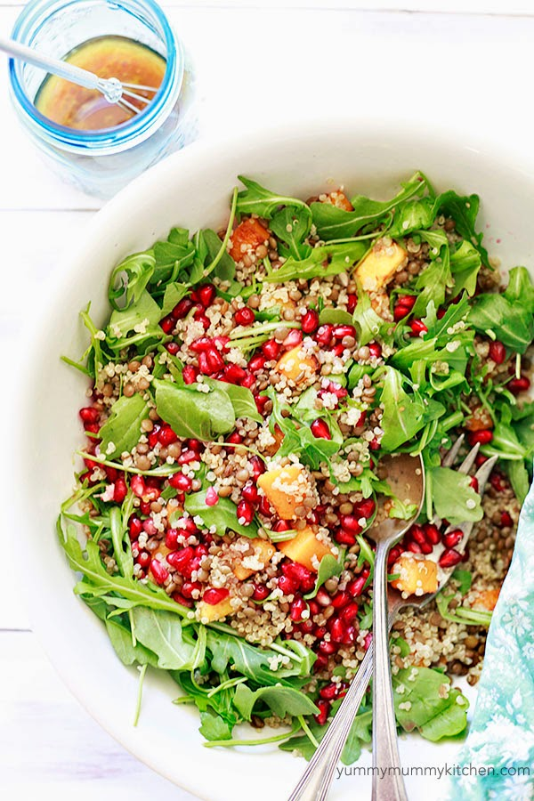 A white bowl filled with a healthy arugula salad with roasted butternut squash, quinoa, lentils and pomegranate.