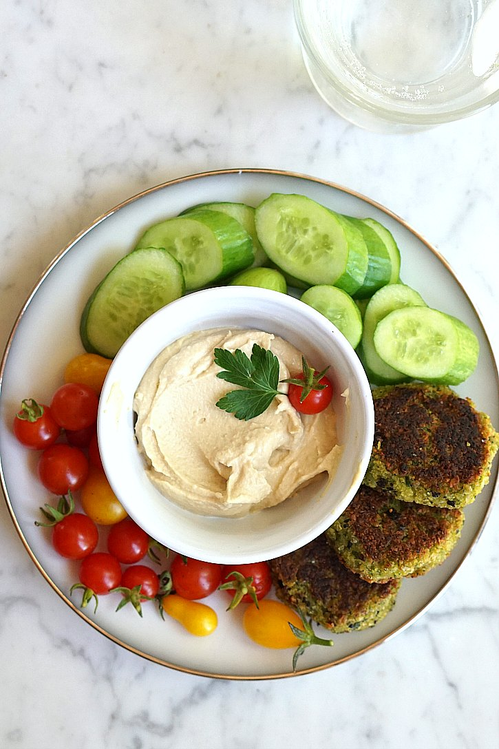 Vegan falafel served with cucumber, tomatoes, and hummus.