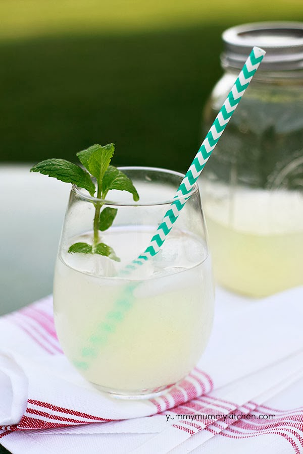 Fresh homemade healthy lemonade in a glass with fresh mint and a paper straw sit on a table outside. This easy lemonade recipe is sugar-free and vegan.