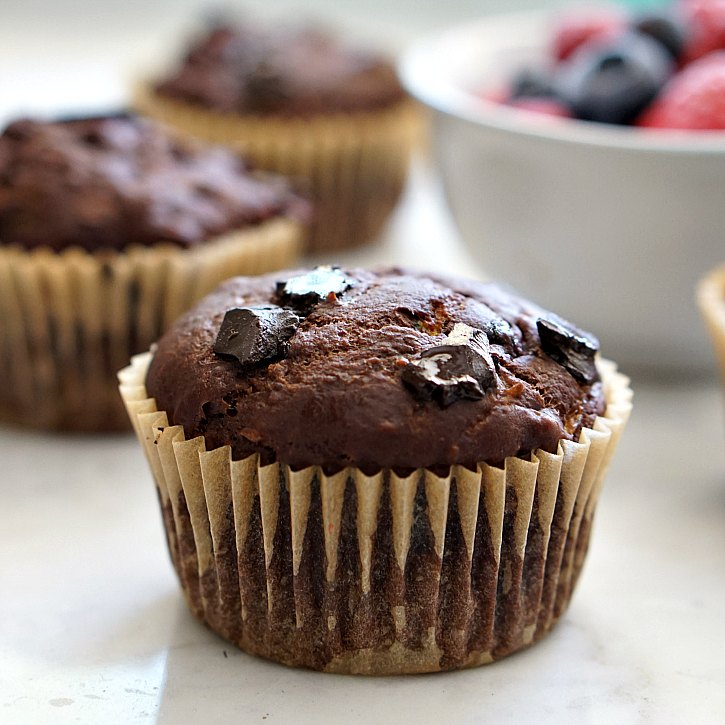 Beautiful vegan double chocolate zucchini muffins with chocolate chunks.