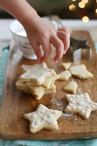 Beautiful vegan sugar cookies topped with white icing and sugar.