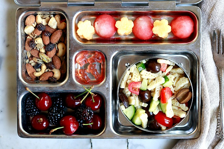 A wholesome kids lunch box with train mix, pasta salad, melon, and Horizon Organic gummies.