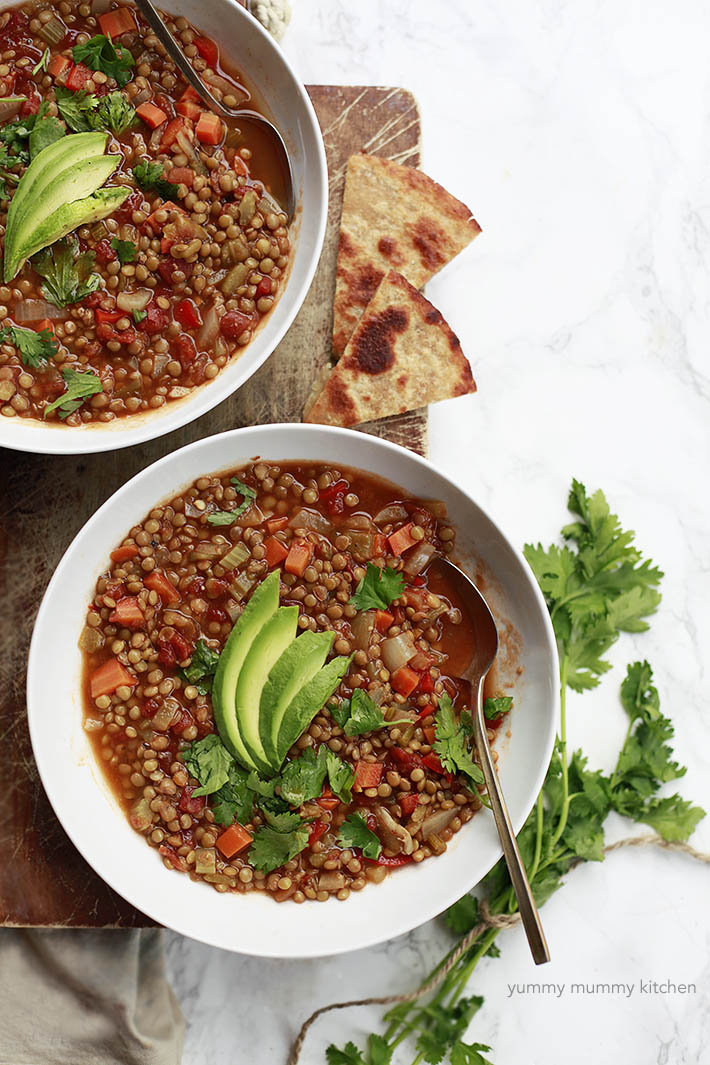Vegetarian and vegan Mexican lentil soup with vegetables and topped with avocado and cilantro.