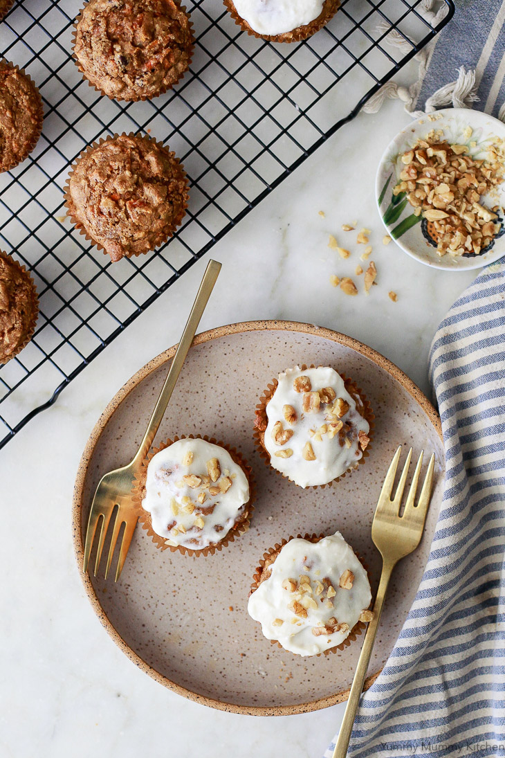 Carrot muffins on a plate with forks. These carrot muffins are frosted with dairy-free cream cheese frosting and topped with walnuts. They are vegan and gluten free.