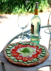 A beautiful rainbow vegetable pizza topped with zucchini, tomatoes, summer squash and onions sits on a patio table with a bottle of white wine.