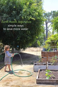 A little girl watering a vegetable garden.