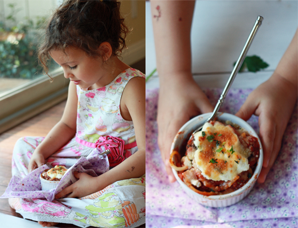 Little girl holding baked spaghetti pie, a kid-friendly recipe.
