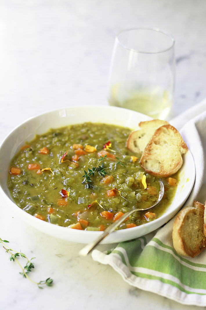 A bowl of vegetarian slow cooker split pea soup with sliced baguette.