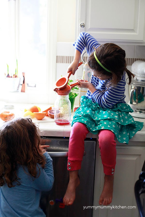 Kids squeeze lemons and blood oranges to make healthy homemade lemonade and orange juice.