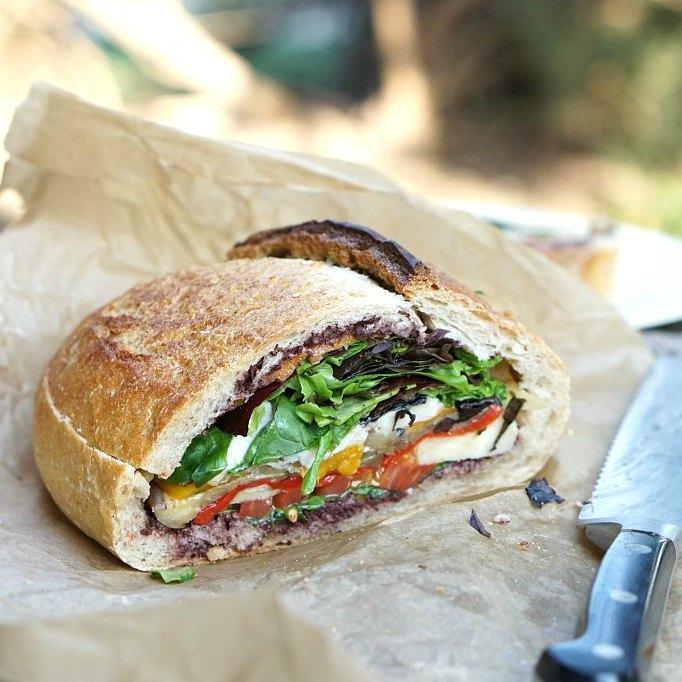 A vegetarian muffuletta style sandwich stuffed with veggies is perfect for picnics.