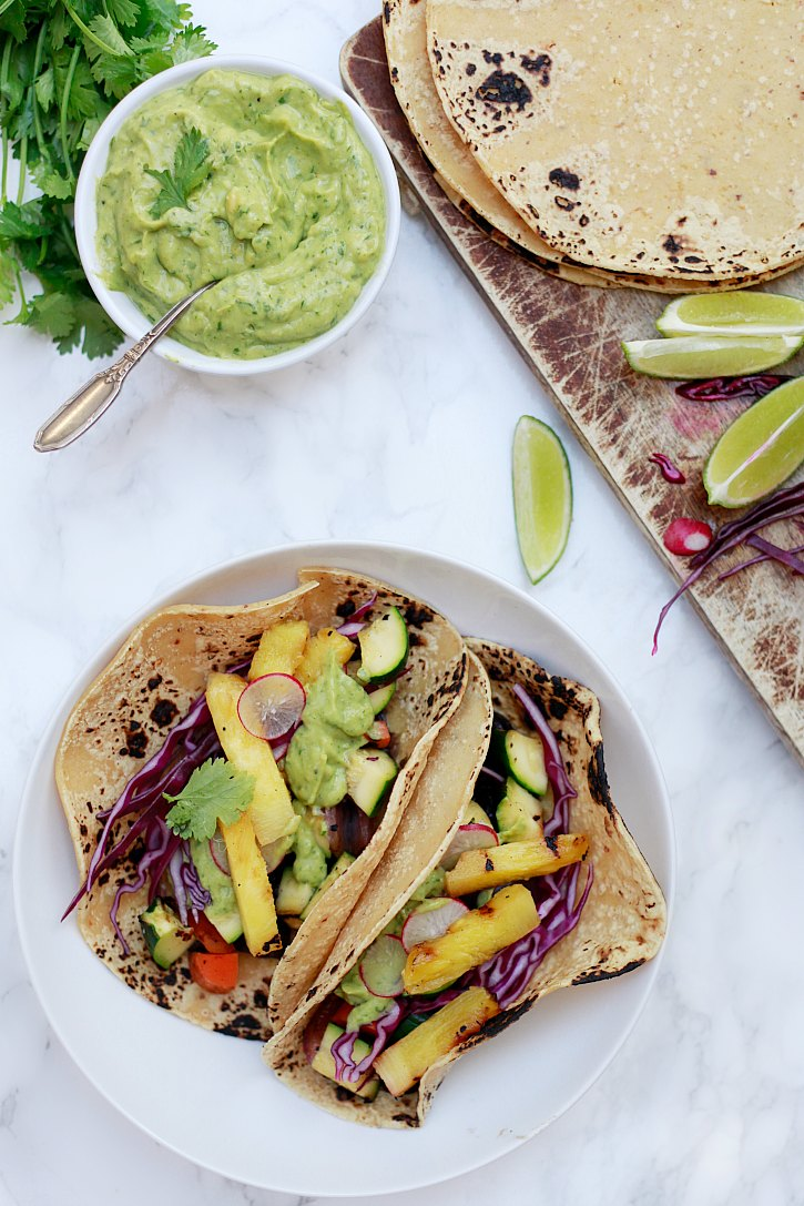 Grilled vegetable tacos and black bean tacos topped with avocado cream sauce, cabbage, sliced radishes, and grilled pineapple makes a beautiful and healthy dinner.