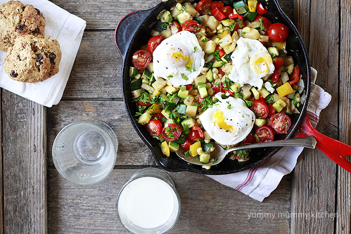 vegetable hash with poached eggs in a red Le Creuset skillet.
