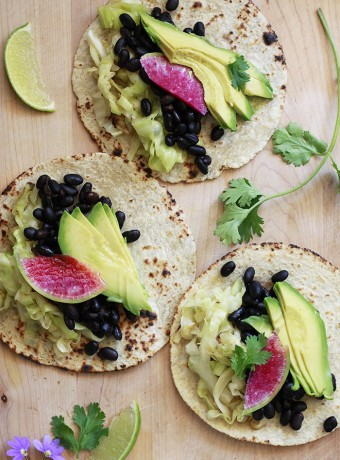beautiful vegan tacos with black beans, cabbage, and avocado