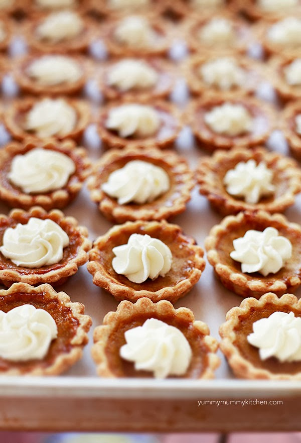A tray full of mini pumpkin pie tarts topped with whipped cream.