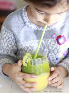 A little girl drinks a tropical kiwi green smoothie.