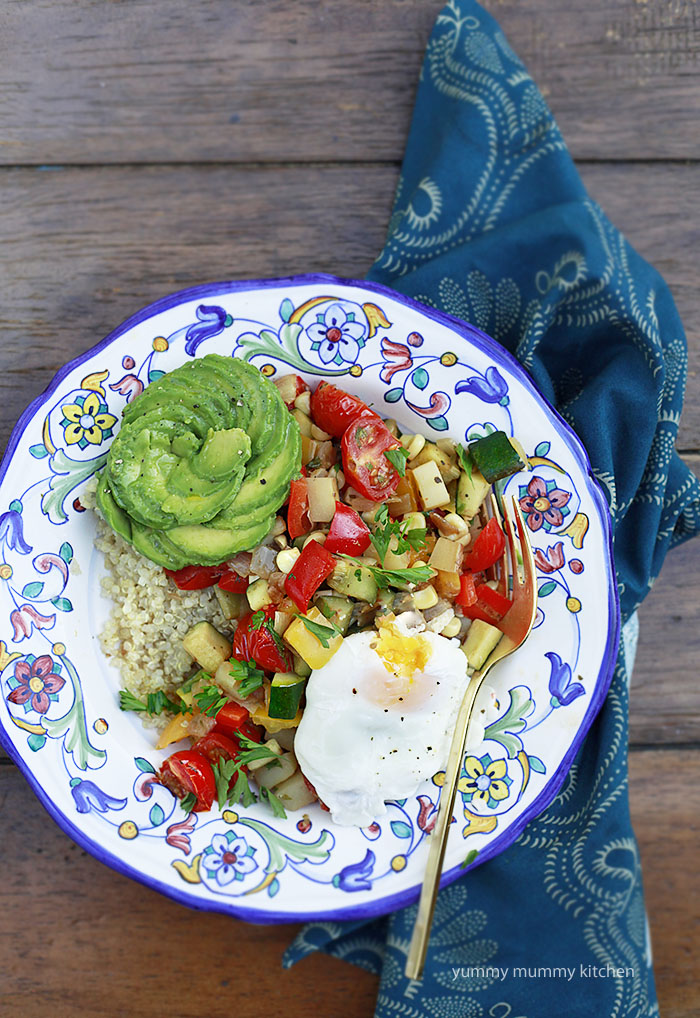 A bowl of summer vegetable hash with poached eggs, quinoa, and avocado.