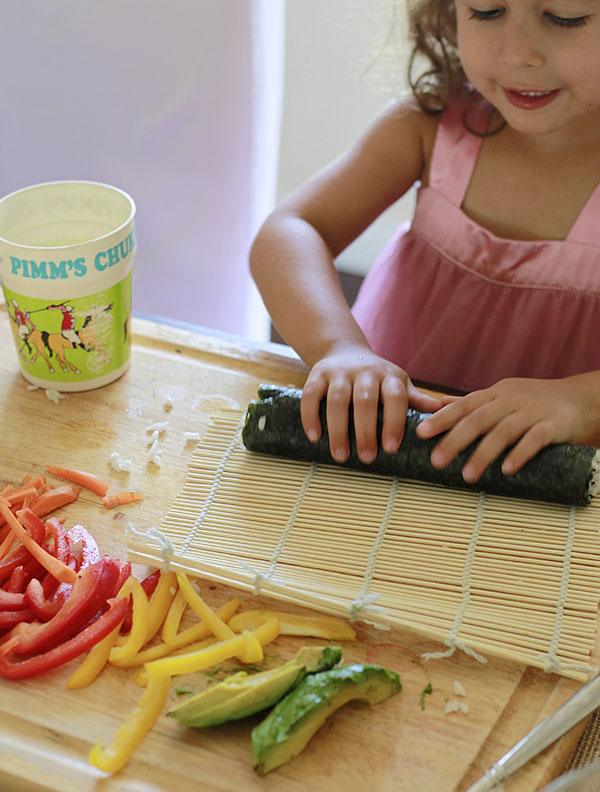 A little girl makes vegan sushi by rolling a sushi roll on a bamboo mat. Vegetables can be seen in the foreground on a cutting board.