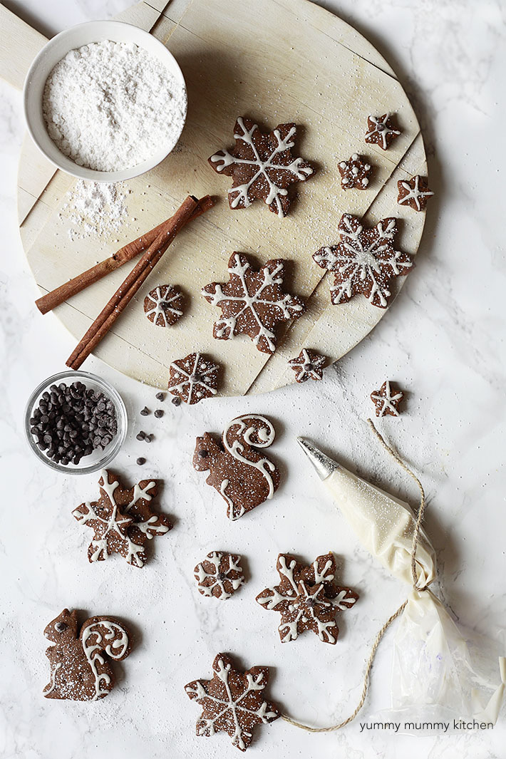 Cute decorated vegan gingerbread cookies sit on a marble countertop.