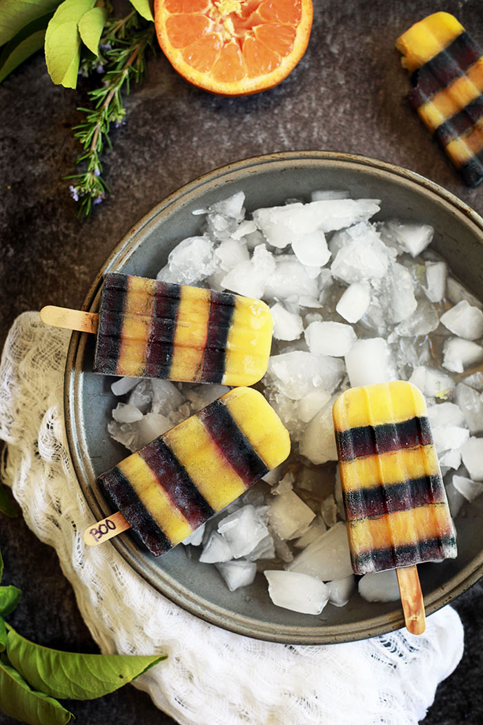 Orange and black striped popsicles are healthier Halloween treat that are vegan.