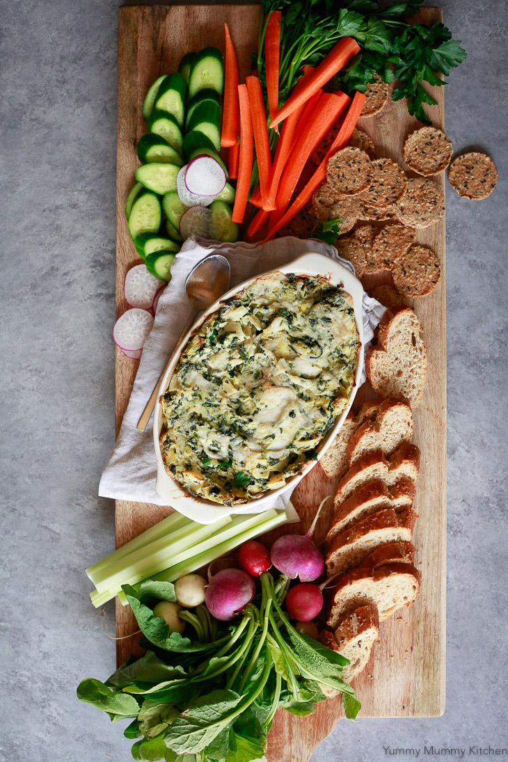 A beautiful crudite platter with vegan baked spinach artichoke dip, vegetables, crackers, and baguette. This dip is so delicious for a vegan and paleo appetizer.