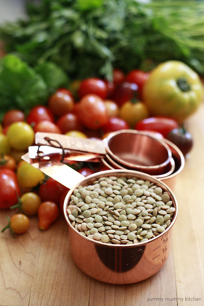 A copper measuring cup filled with green lentils next to tomatoes and parsley on a cutting board.