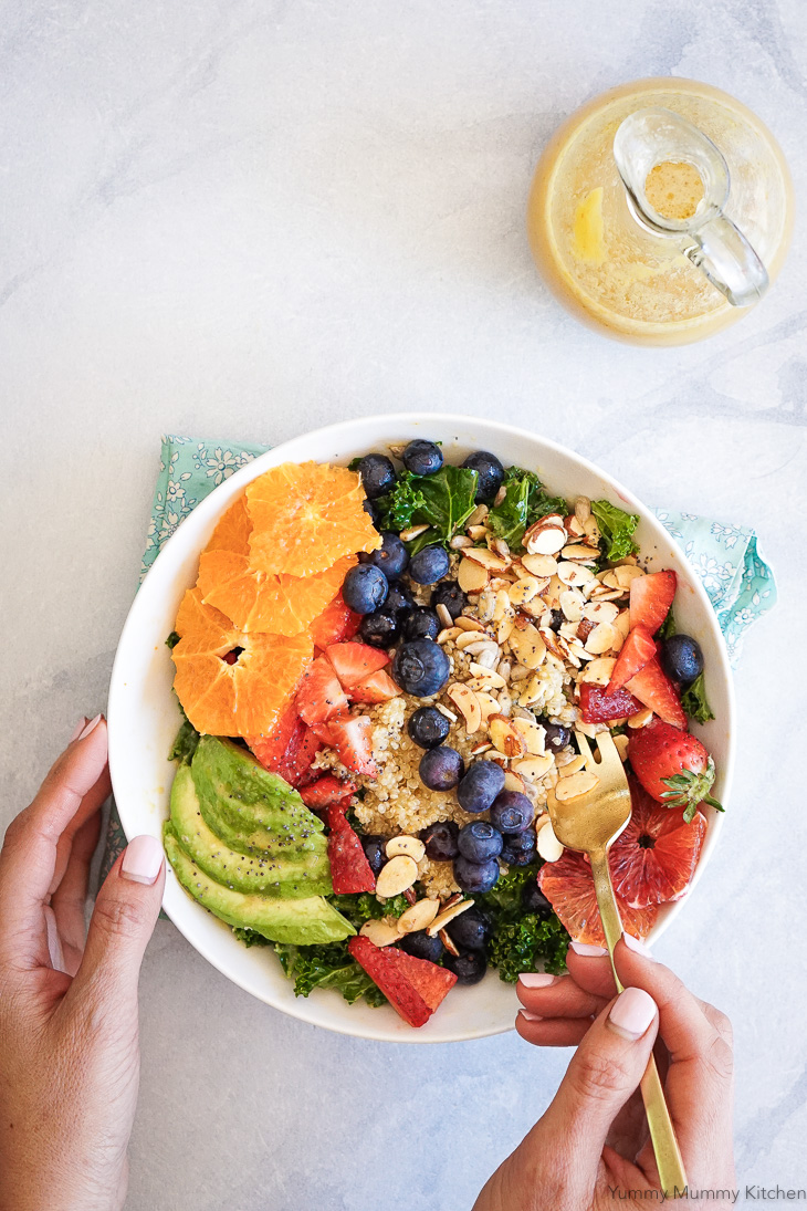A beautiful healthy salad with kale, quinoa, berries, avocado and an easy orange vinaigrette dressing made in the blender.