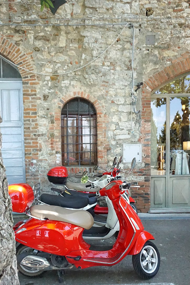 Vespas line a street in Tuscany.