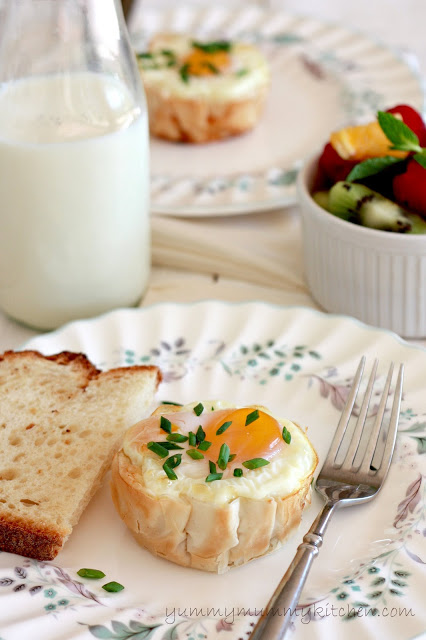 Egg baked in a filo dough cup on a floral plat with toast and fresh fruit in the background.