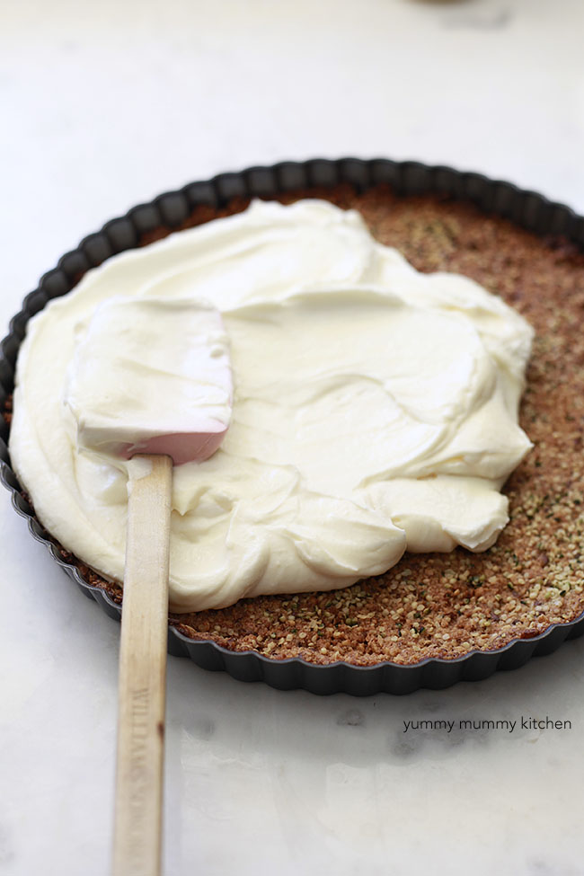 Spreading the lemon curd yogurt mixture into the granola crust.