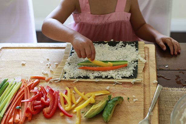 A child places thinly sliced vegetables on top of a sheet of nori covered with sushi rice.