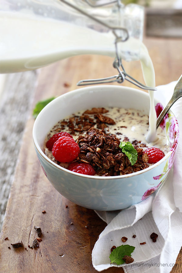 A bowl of chocolate granola with milk, fresh raspberries, and mint.