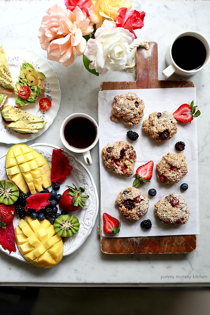 A beautiful brunch spread with tropical fruit, avocado toast, and homemade oatmeal scones.