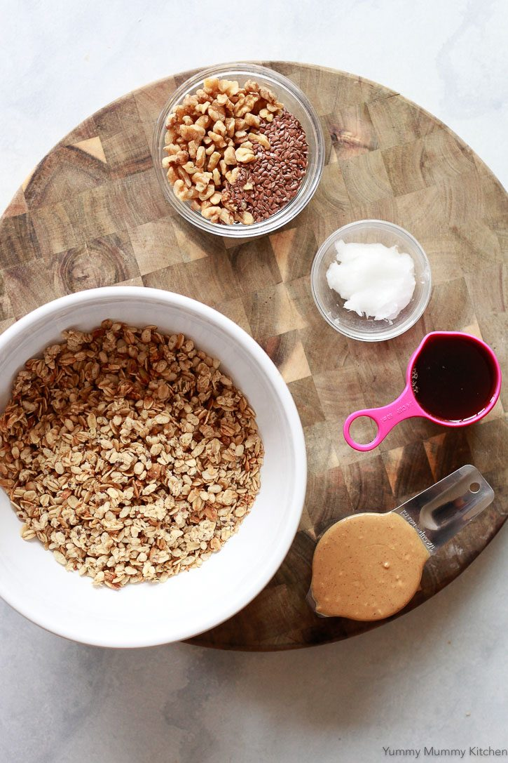 Ingredients for crunchy homemade no-bake granola bars include pre-made granola, peanut butter, maple syrup, flax, and coconut oil.