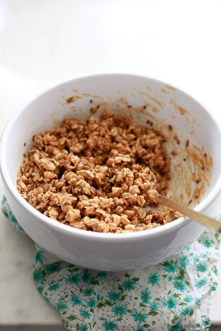 The ingredients for no-bake crunchy granola bars get mixed together in a white bowl.