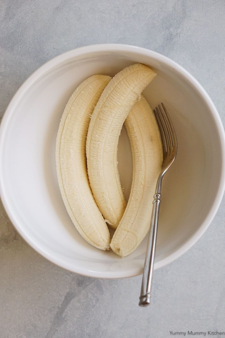 Three peeled bananas in a white bowl ready to be mashed.