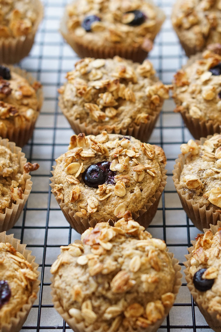 Beautiful granola banana muffins with blueberries on a cooling rack.