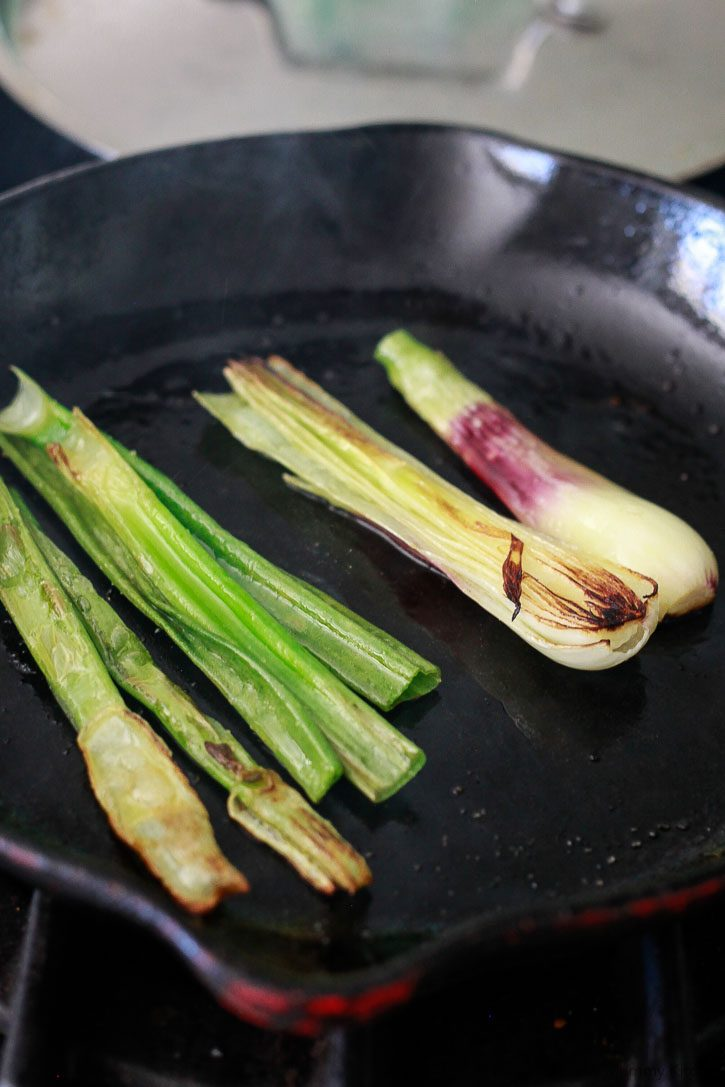 Spring onions get charred on a stovetop skillet.