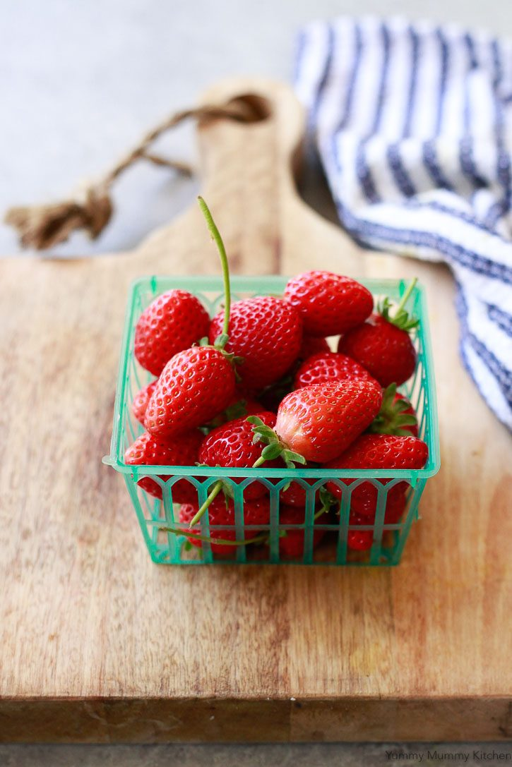 A green farmers market basket of fresh strawberries sitting on a cutting board with a blue and white dish towel.