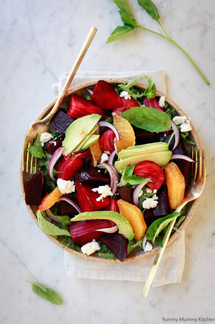 Beautiful roasted beet salad with avocado, orange segments, red onion, basil, and arugula.