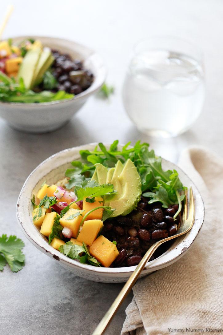 Beautiful vegan bowls filled with Cuban black beans, mango salsa, avocado, and rice.