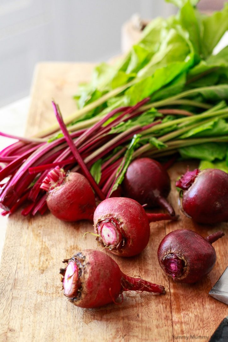 Beet greens get cut off from beet roots before the roots are roasted in the oven.