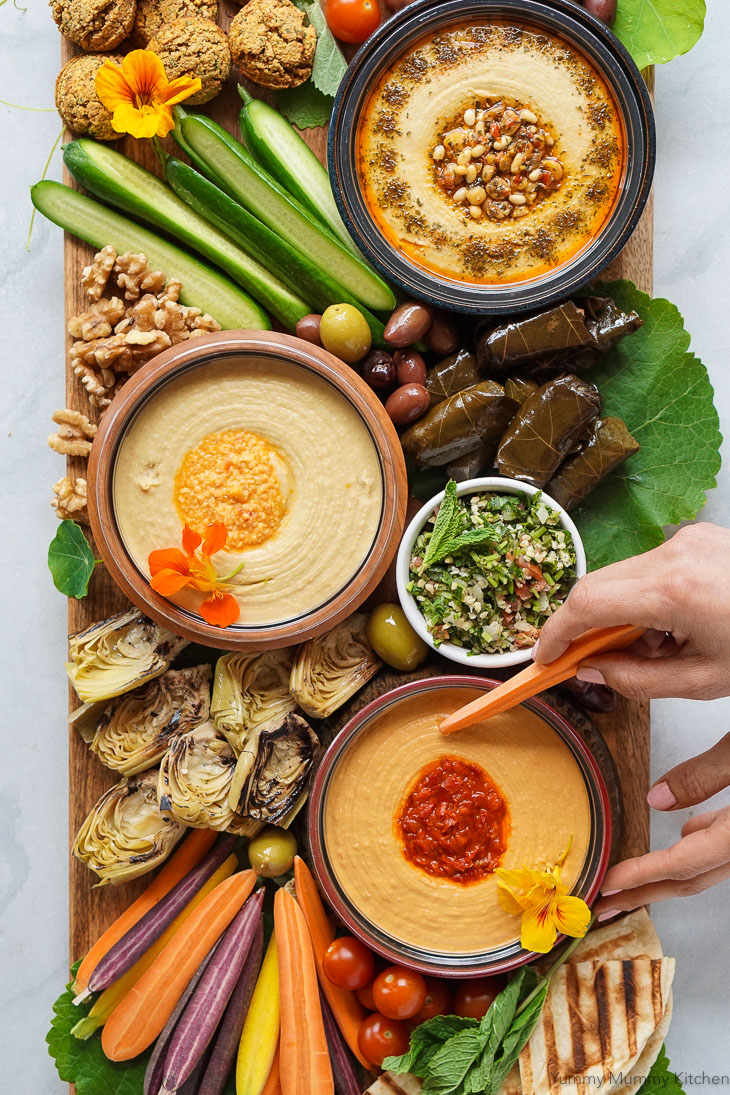 A beautiful mezze platter with hummus, cold vegetables, falafel, and flatbread is perfect as an appetizer board for parties.