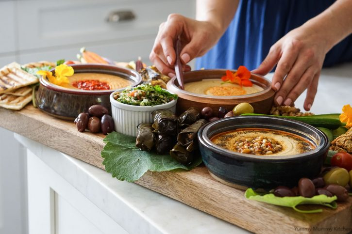 A hummus platter with stuffed grape leaves, vegetables, tabbouleh and olives in a white kitchen.