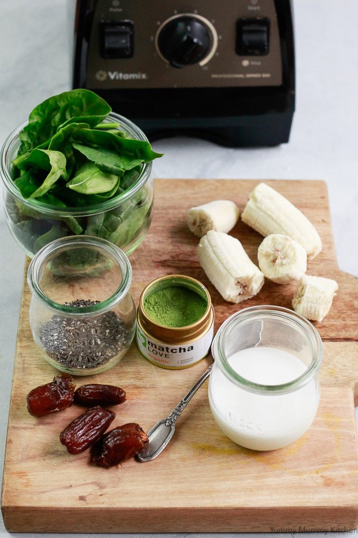 The ingredients for a healthy matcha smoothie are set on a cutting board and include almond milk, matcha powder, bananas, chia seeds, dates, and spinach.