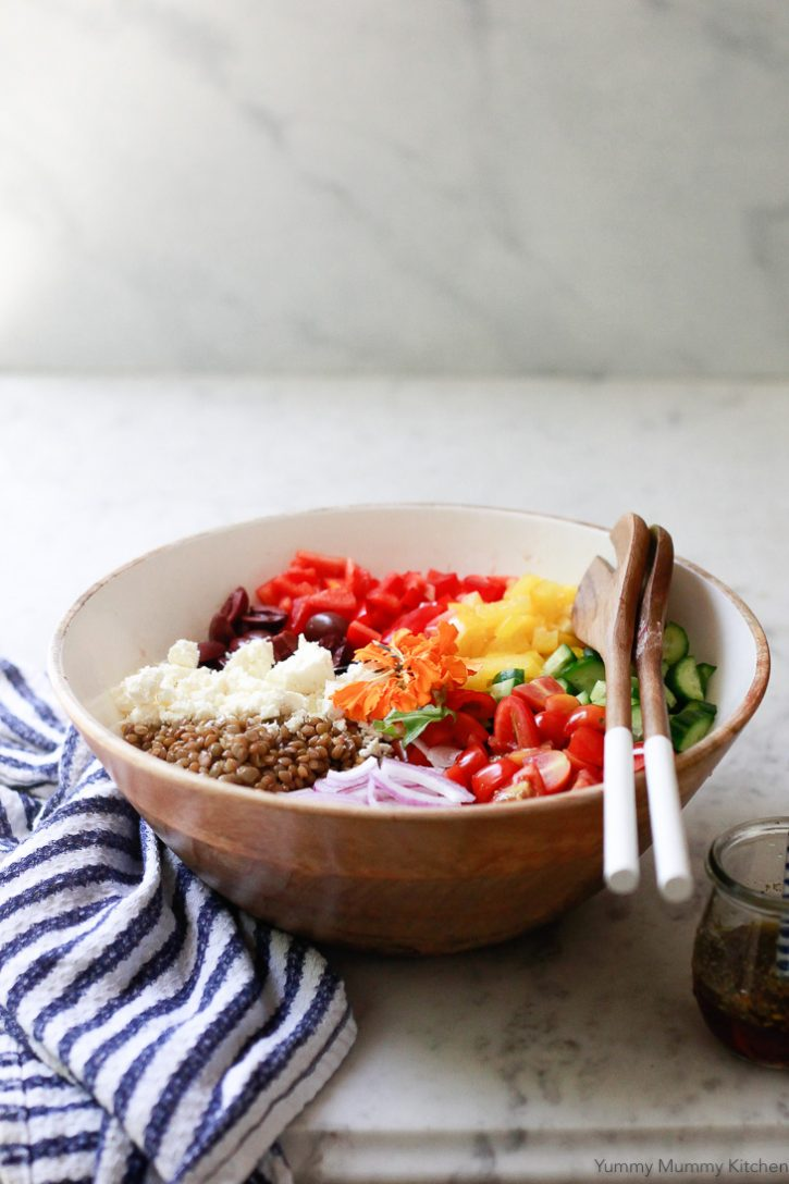 A beautiful colorful Mediterranean lentil salad in a wooden salad bowl.