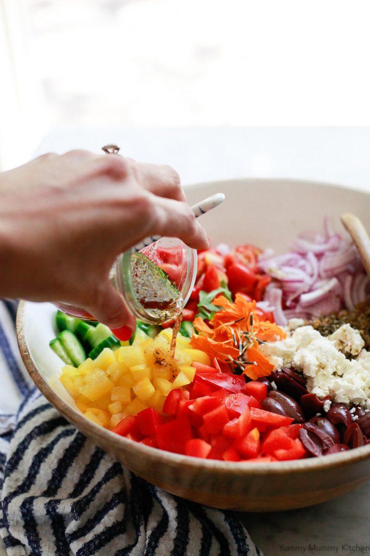 A Greek style red wine vinaigrette gets poured over a Mediterranean lentil salad with feta, cucumber, bell pepper, and olives.