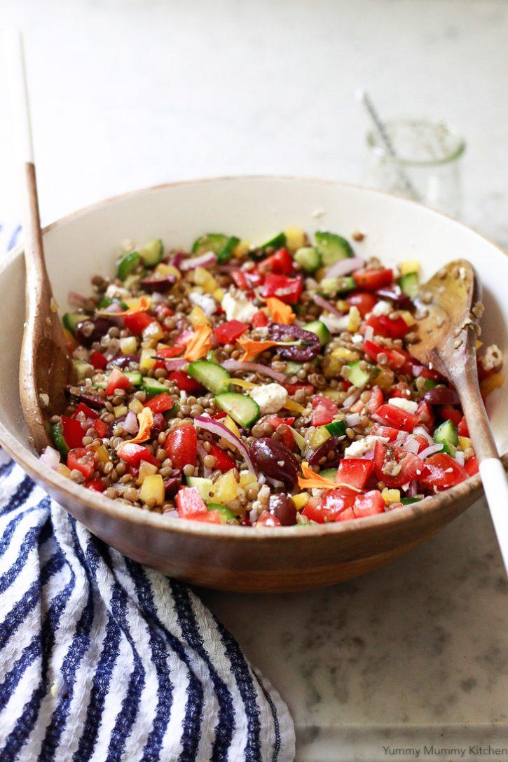 A delicious tossed Mediterranean lentil salad in a wooden salad bowl. This colorful lentil salad is naturally vegetarian or vegan.